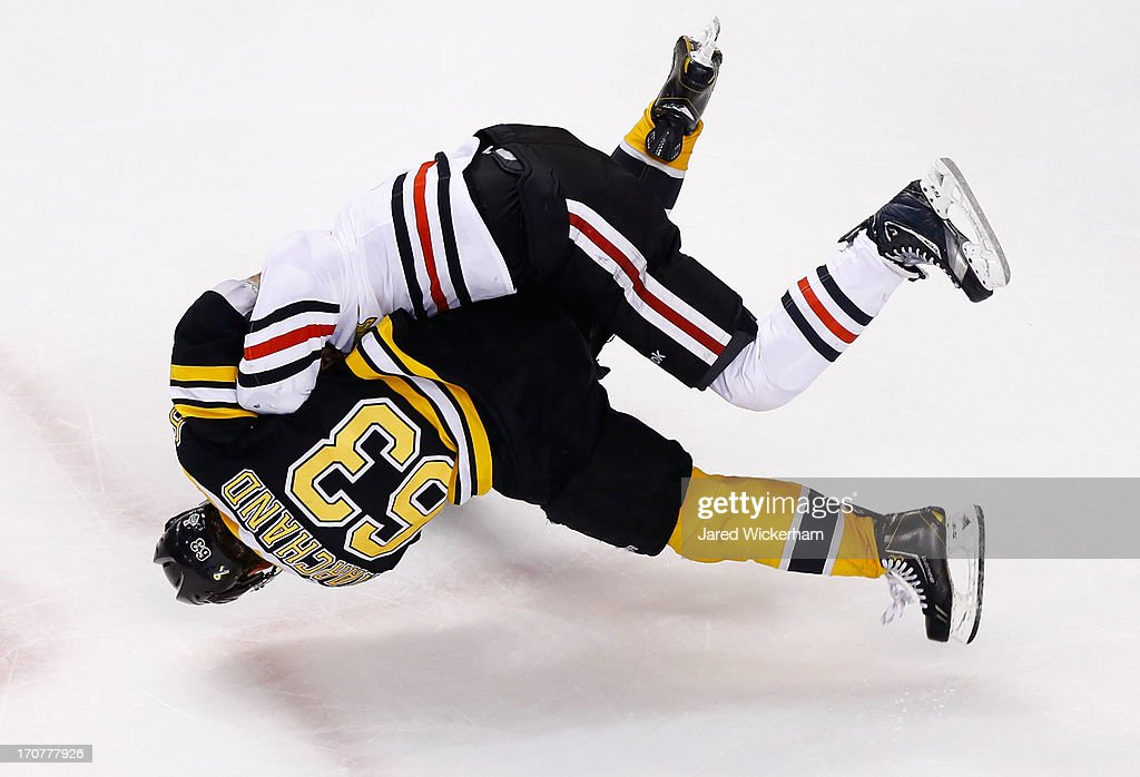 Brad Marchand of the Boston Bruins and Andrew Shaw of the Chicago Blackhawks go airborne while fighting toward the end of the third period in Game...