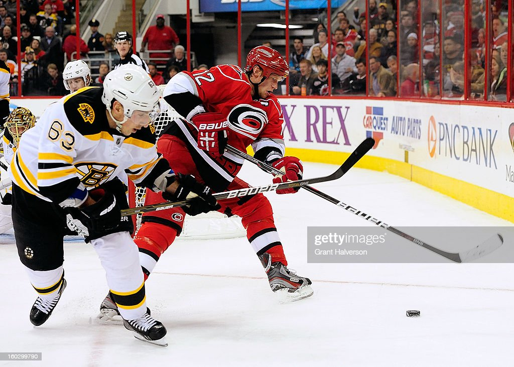 Brad Marchand #63 of the Boston Bruins and Eric Staal #12 of the Carolina Hurricanes chase a loose puck behind the net during play at PNC Arena on January 28, 2013 in Raleigh, North Carolina.