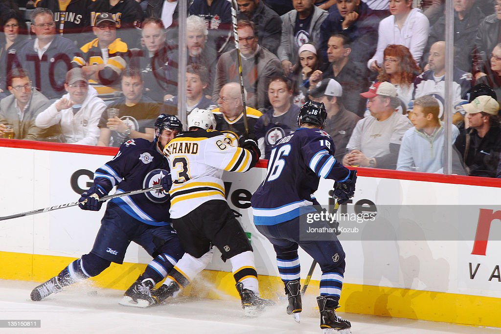<a gi-track='captionPersonalityLinkClicked' href=/galleries/search?phrase=Brad+Marchand&family=editorial&specificpeople=2282544 ng-click='$event.stopPropagation()'>Brad Marchand</a> #63 of the Boston Bruins battles along the boards with <a gi-track='captionPersonalityLinkClicked' href=/galleries/search?phrase=Tanner+Glass&family=editorial&specificpeople=4596666 ng-click='$event.stopPropagation()'>Tanner Glass</a> #15 and <a gi-track='captionPersonalityLinkClicked' href=/galleries/search?phrase=Andrew+Ladd&family=editorial&specificpeople=228452 ng-click='$event.stopPropagation()'>Andrew Ladd</a> #16 of the Winnipeg Jets during third period action at the MTS Centre on December 6, 2011 in Winnipeg, Manitoba, Canada.