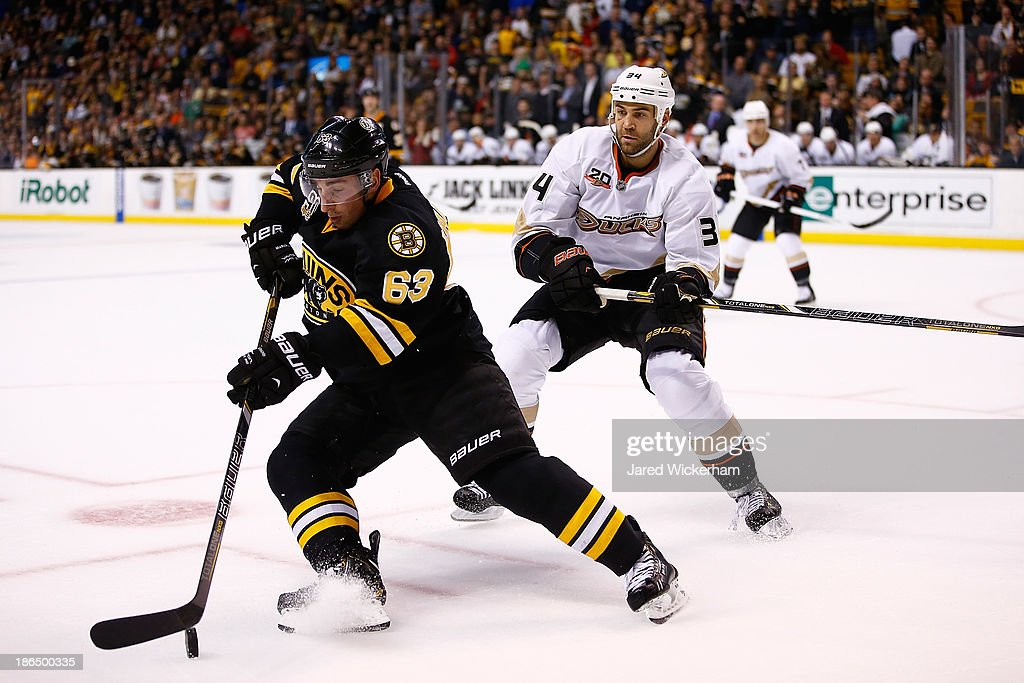 Brad Marchand #63 of the Boston Bruins carries the puck in front of Daniel Winnik #34 of the Anaheim Ducks in the third period at TD Garden on October 31, 2013 in Boston, Massachusetts.