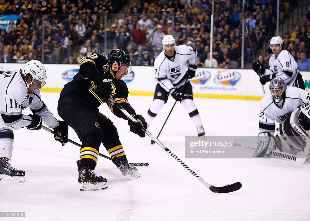 Brad Marchand of the Boston Bruins carries the puck past Anze Kopitar of the Los Angeles Kings in the first period before scoring shorthanded during...