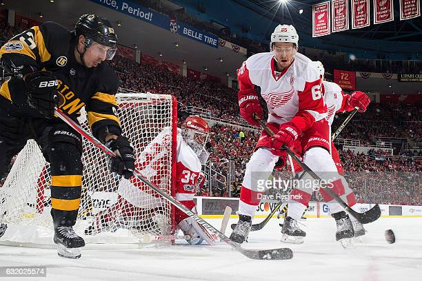 Brad Marchand of the Boston Bruins chases after a loose puck with Danny DeKeyser of the Detroit Red Wings in front of teammate goaltender Petr Mrazek...