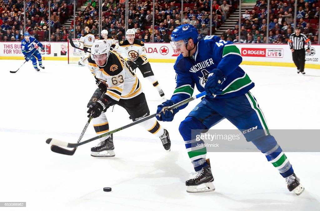 Brad Marchand #63 of the Boston Bruins checks Drew Shore #42 of the Vancouver Canucks during their NHL game at Rogers Arena March 13, 2017 in Vancouver, British Columbia, Canada. Boston won 6-3.