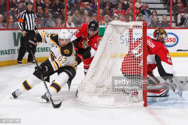 Brad Marchand of the Boston Bruins controls the puck behind the net on a wraparound attempt against Ben Harpur and Craig Anderson of the Ottawa...