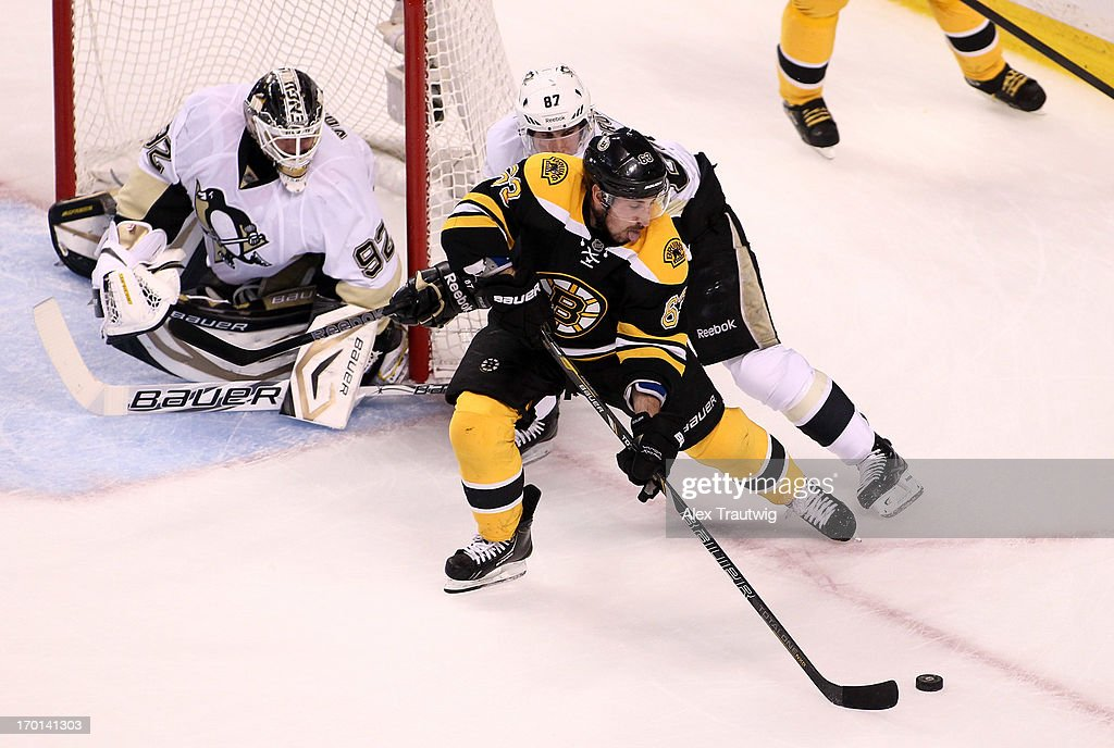 Brad Marchand #63 of the Boston Bruins handles the puck in front of the net against Sidney Crosby #87 and Tomas Vokoun #92 of the Pittsburgh Penguins in the first period in Game Four of the Eastern Conference Final during the 2013 Stanley Cup Playoffs at TD Garden on June 7, 2013 in Boston, Massachusetts.