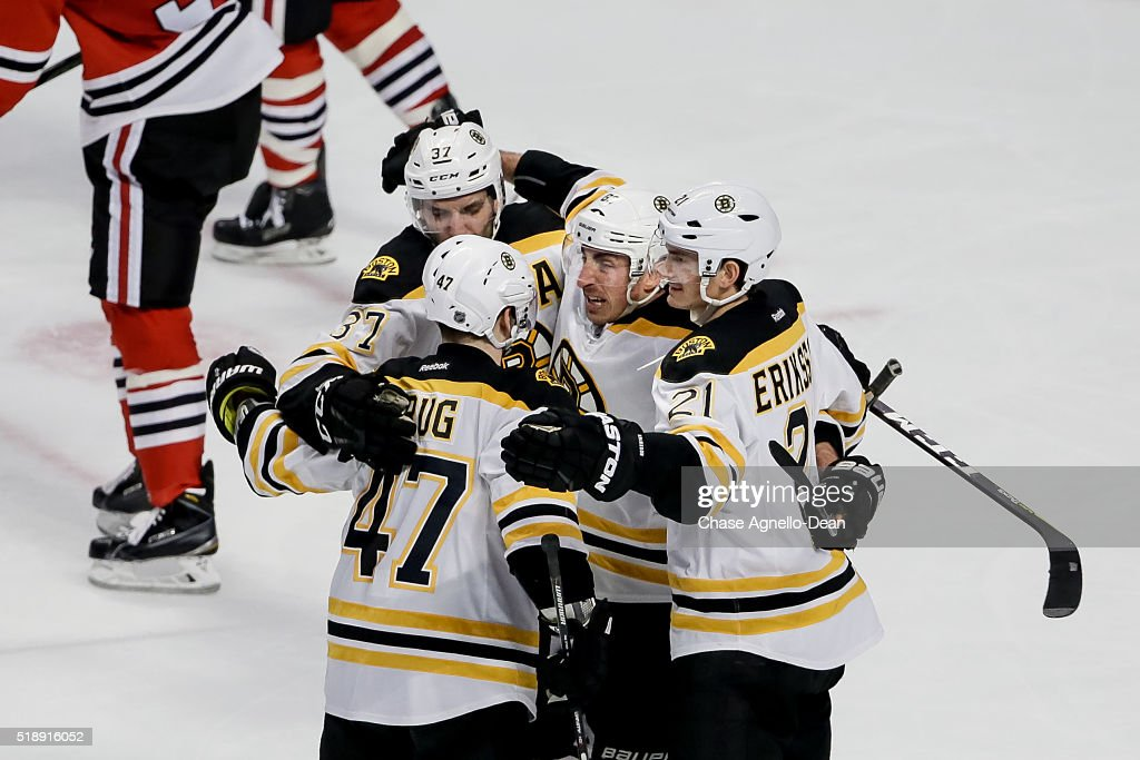 Brad Marchand #63 of the Boston Bruins (middle) hugs Patrice Bergeron #37, Torey Krug #47 and Loui Eriksson #21 after scoring against the Chicago Blackhawks in the third period of the NHL game at the United Center on April 3, 2016 in Chicago, Illinois.