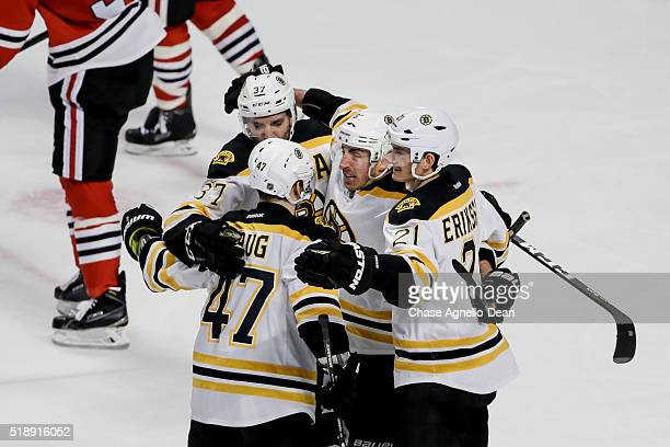 Brad Marchand of the Boston Bruins hugs Patrice Bergeron Torey Krug and Loui Eriksson after scoring against the Chicago Blackhawks in the third...