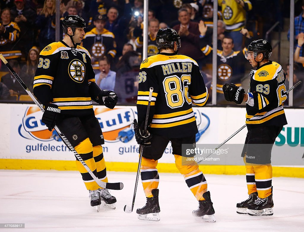 <a gi-track='captionPersonalityLinkClicked' href=/galleries/search?phrase=Brad+Marchand&family=editorial&specificpeople=2282544 ng-click='$event.stopPropagation()'>Brad Marchand</a> #63 of the Boston Bruins is congratulated by teammates <a gi-track='captionPersonalityLinkClicked' href=/galleries/search?phrase=Zdeno+Chara&family=editorial&specificpeople=203177 ng-click='$event.stopPropagation()'>Zdeno Chara</a> #33 and <a gi-track='captionPersonalityLinkClicked' href=/galleries/search?phrase=Kevan+Miller&family=editorial&specificpeople=8236132 ng-click='$event.stopPropagation()'>Kevan Miller</a> #86 following his empty-net goal in the third period against the Washington Capitals during the game at TD Garden on March 6, 2014 in Boston, Massachusetts.