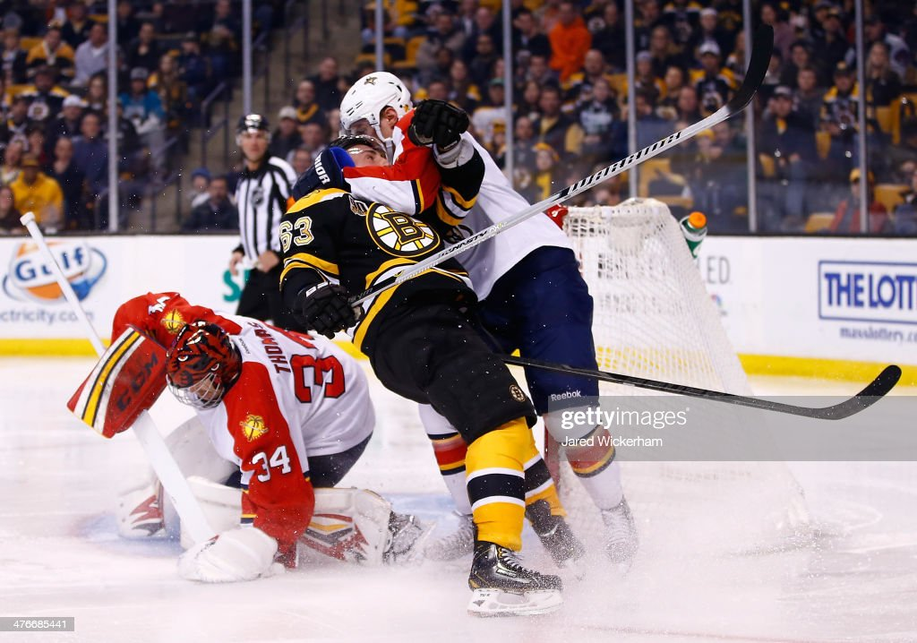 Brad Marchand of the Boston Bruins is hit by Dmitry Kulikov in front of Tim Thomas of the Florida Panthers in the third period during the game at TD...