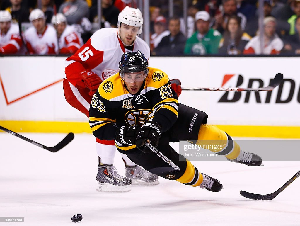 Brad Marchand of the Boston Bruins is tripped up while reaching for the puck in front of Riley Sheahan of the Detroit Red Wings in the first period...