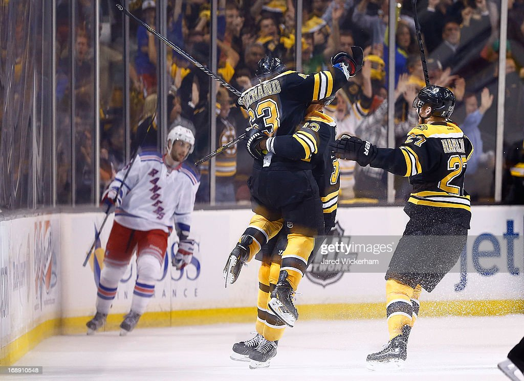 <a gi-track='captionPersonalityLinkClicked' href=/galleries/search?phrase=Brad+Marchand&family=editorial&specificpeople=2282544 ng-click='$event.stopPropagation()'>Brad Marchand</a> #63 of the Boston Bruins jumps into the arms of <a gi-track='captionPersonalityLinkClicked' href=/galleries/search?phrase=Zdeno+Chara&family=editorial&specificpeople=203177 ng-click='$event.stopPropagation()'>Zdeno Chara</a> #33 of the Boston Bruins following his overtime goal against the New York Rangers in Game One of the Eastern Conference Semifinals during the 2013 NHL Stanley Cup Playoffs on May 16, 2013 at TD Garden in Boston, Massachusetts.