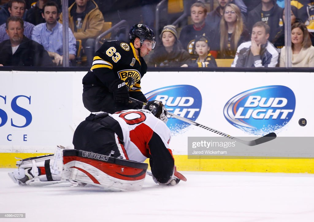 <a gi-track='captionPersonalityLinkClicked' href=/galleries/search?phrase=Brad+Marchand&family=editorial&specificpeople=2282544 ng-click='$event.stopPropagation()'>Brad Marchand</a> #63 of the Boston Bruins knock the puck ahead of <a gi-track='captionPersonalityLinkClicked' href=/galleries/search?phrase=Robin+Lehner&family=editorial&specificpeople=5894610 ng-click='$event.stopPropagation()'>Robin Lehner</a> #40 of the Ottawa Senators in the first period during the game at TD Garden on December 27, 2013 in Boston, Massachusetts.