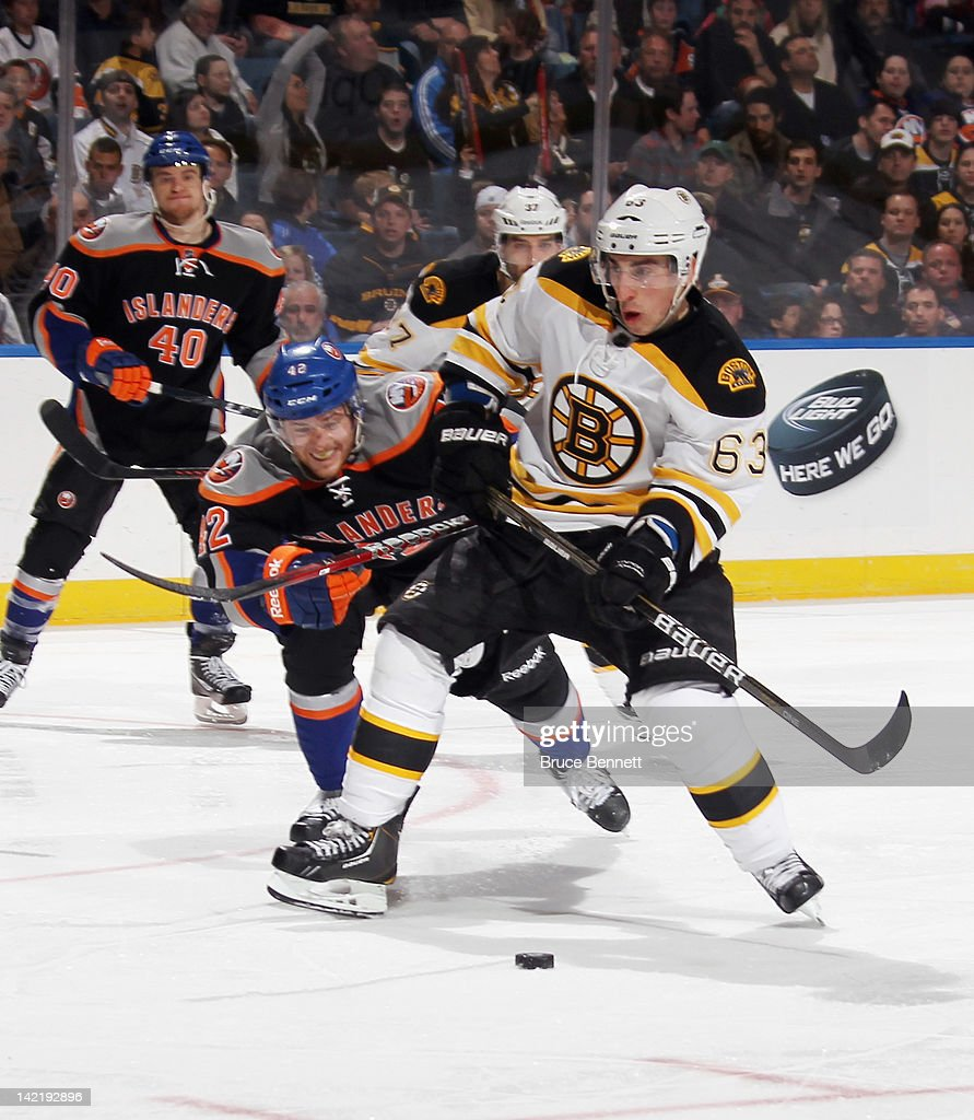 <a gi-track='captionPersonalityLinkClicked' href=/galleries/search?phrase=Brad+Marchand&family=editorial&specificpeople=2282544 ng-click='$event.stopPropagation()'>Brad Marchand</a> #63 of the Boston Bruins moves past Dylan Reese #42 of the New York Islanders at the Nassau Veterans Memorial Coliseum on March 31, 2012 in Uniondale, New York. The Bruins defeated the Islanders 6-3.