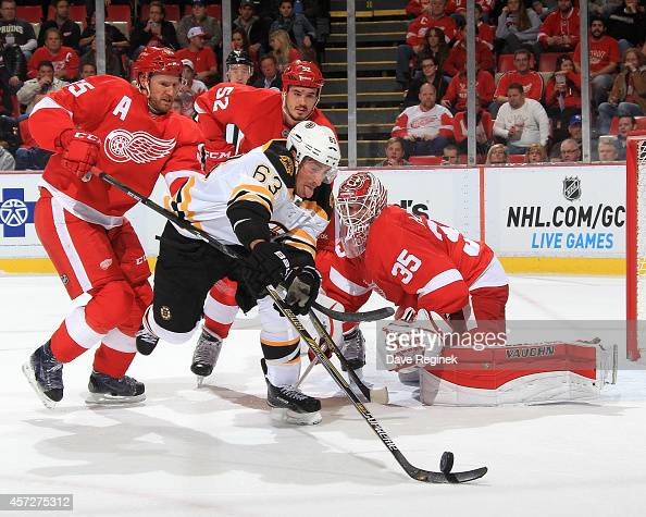 Brad Marchand of the Boston Bruins reaches for the puck as Niklas Kronwall Jonathan Ericsson and Jimmy Howard of the Detroit Red Wings all close in...