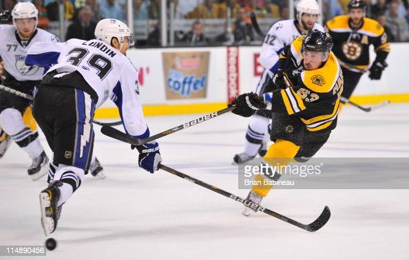 Brad Marchand of the Boston Bruins shoots the puck against Mike Lundin of the Tampa Bay Lightning in Game Seven of the Eastern Conference Finals...