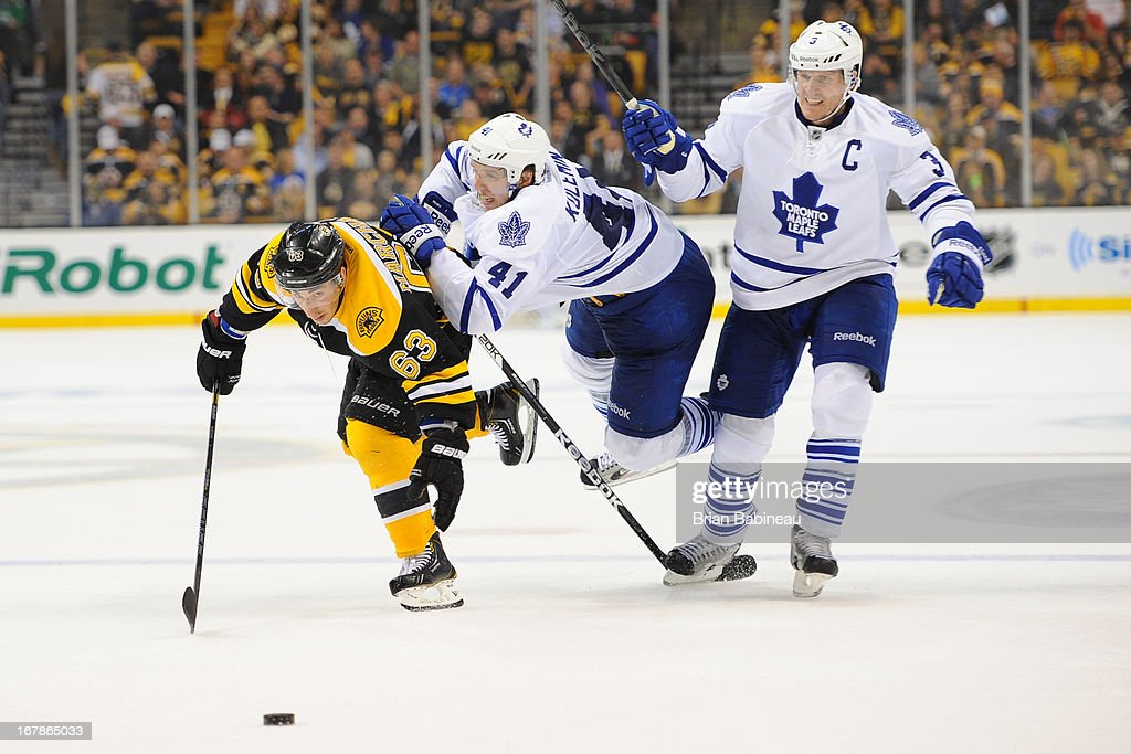 <a gi-track='captionPersonalityLinkClicked' href=/galleries/search?phrase=Brad+Marchand&family=editorial&specificpeople=2282544 ng-click='$event.stopPropagation()'>Brad Marchand</a> #63 of the Boston Bruins skates against <a gi-track='captionPersonalityLinkClicked' href=/galleries/search?phrase=Nikolai+Kulemin&family=editorial&specificpeople=537949 ng-click='$event.stopPropagation()'>Nikolai Kulemin</a> #41 and <a gi-track='captionPersonalityLinkClicked' href=/galleries/search?phrase=Dion+Phaneuf&family=editorial&specificpeople=545455 ng-click='$event.stopPropagation()'>Dion Phaneuf</a> #3 of the Toronto Maple Leafs in Game One of the Eastern Conference Quarterfinals during the 2013 NHL Stanley Cup Playoffs at TD Garden on May 1, 2013 in Boston, Massachusetts.