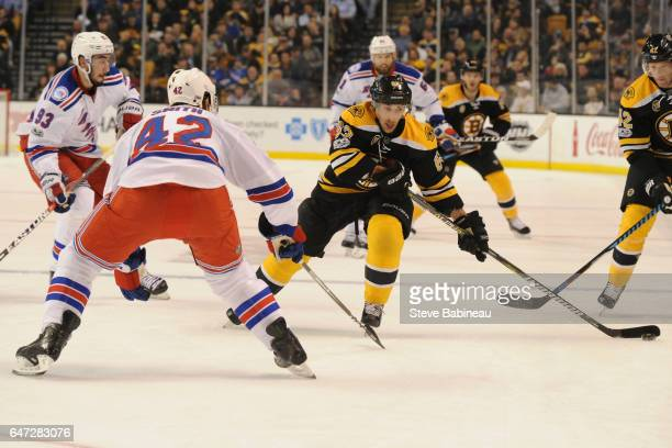 Brad Marchand of the Boston Bruins skates with the puck against Brendan Smith of the New York Rangers at the TD Garden on March 2 2017 in Boston...