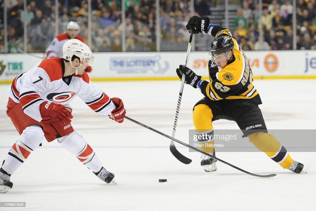 Brad Marchand of the Boston Bruins skates with the puck against Ryan Murphy of the Carolina Hurricanes at the TD Garden on March 15 2014 in Boston...