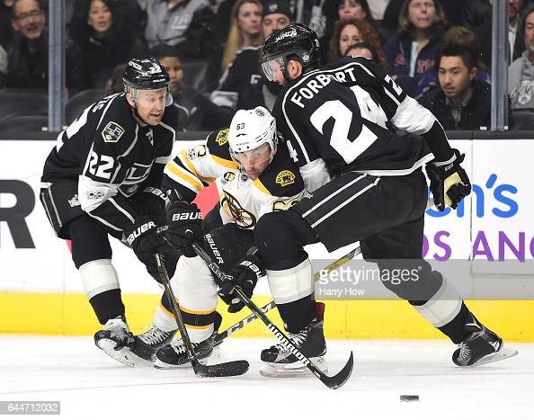 Brad Marchand of the Boston Bruins splits the defense of Derek Forbort and lTrevor Lewis of the Los Angeles Kings during the first period at Staples...