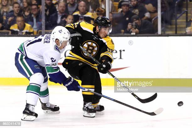 Brad Marchand of the Boston Bruins takes a shot against Troy Stecher of the Vancouver Canucks during the third period at TD Garden on October 19 2017...