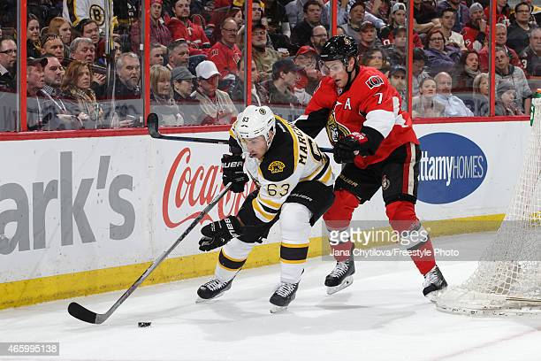 Brad Marchand of the Boston Bruins uses his body to protect the pic from Kyle Turris of the Ottawa Senators at Canadian Tire Centre on March 10 2015...