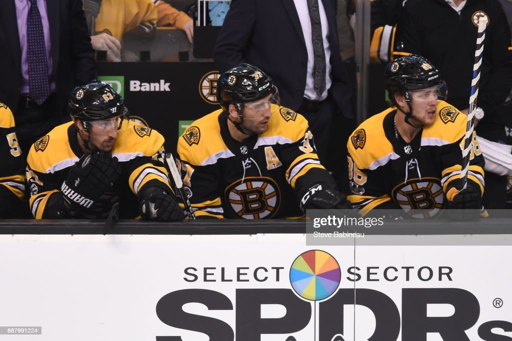Brad Marchand #63, Patrice Bergeron #37 and David Pastrnak #88 of the Boston Bruins watch the play from the bench against the Arizona Coyotes at the TD Garden on December 7, 2017 in Boston, Massachusetts.