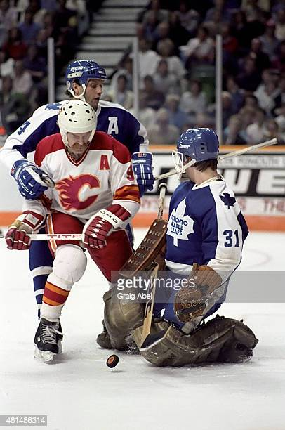 Brad Maxwell and goalie Ken Wregget of the Toronto Maple Leafs fight for the puck with Lanny MacDonald of the Calgary Flames during NHL game action...