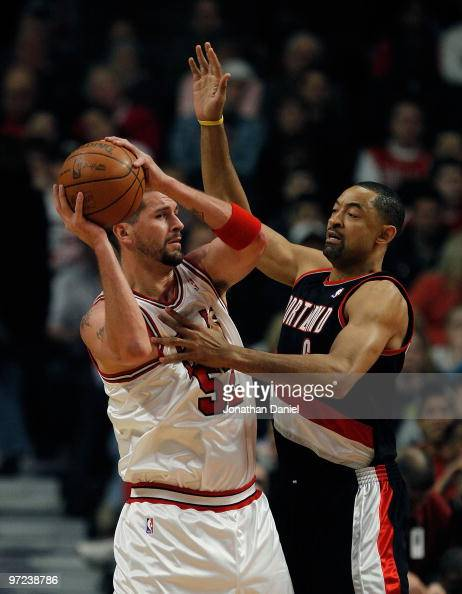 Brad Miller of the Chicago Bulls looks to pass under pressure from Juwan Howard of the Portland Trail Blazers at the United Center on February 26...