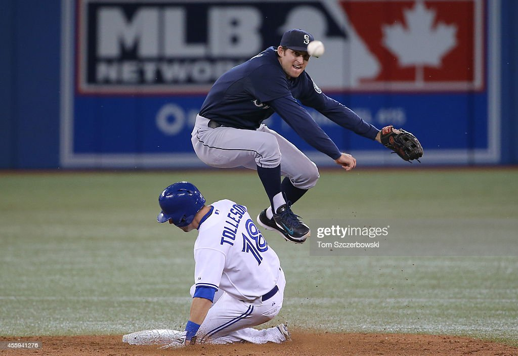 Brad Miller #5 of the Seattle Mariners gets the force out at second base but cannot turn the double play in the eighth inning during MLB game action as Steve Tolleson #18 of the Toronto Blue Jays slides on September 22, 2014 at Rogers Centre in Toronto, Ontario, Canada.