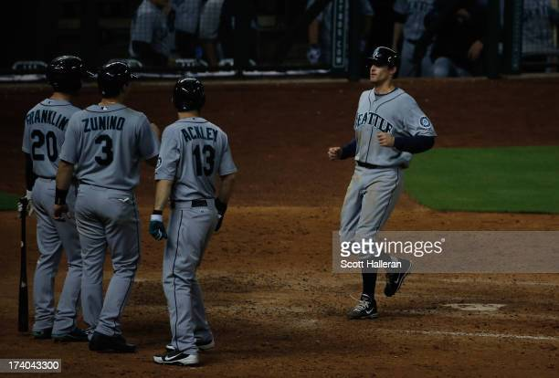 Brad Miller of the Seattle Mariners is greeted by his teammates after a three run homer in the eighth inning against the Houston Astros at Minute...