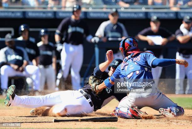 Brad Miller of the Seattle Mariners is tagged out at home plate by catcher Robinson Chirinos of the Texas Rangers during the fifth inning of the...