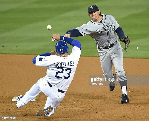 Brad Miller of the Seattle Mariners makes a throw over Adrian Gonzalez of the Los Angeles Dodgers to complete a double play to end the seventh inning...