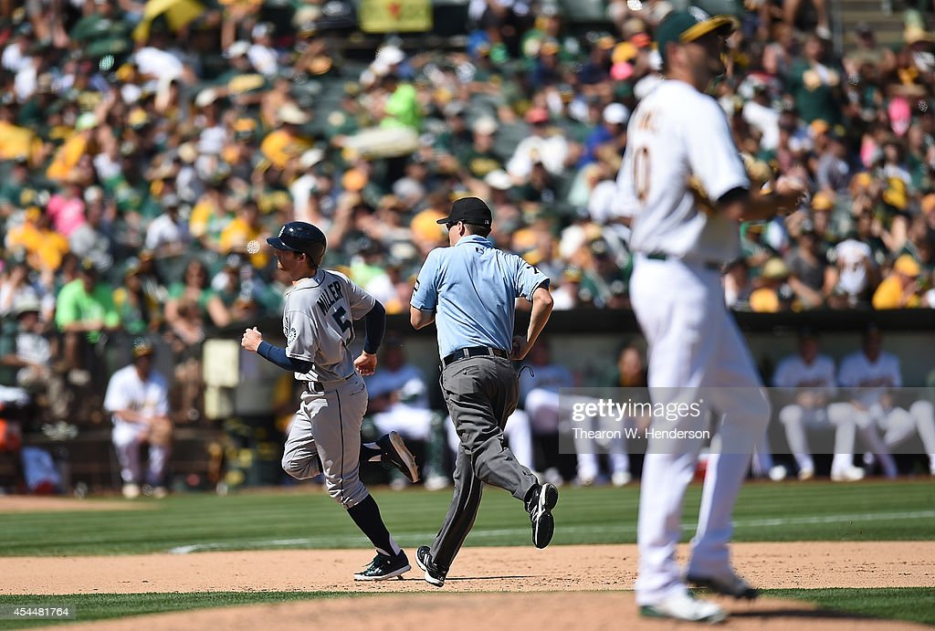 Brad Miller #5 of the Seattle Mariners rounds the bases after hitting a solo home run off of Jason Hammel #40 of the Oakland Athletics in the top of the sixth inning at O.co Coliseum on September 1, 2014 in Oakland, California.