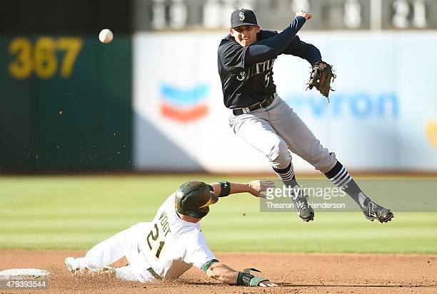 Brad Miller of the Seattle Mariners throws over the top of Stephen Vogt of the Oakland Athletics but not in time to complete the doubleplay in the...