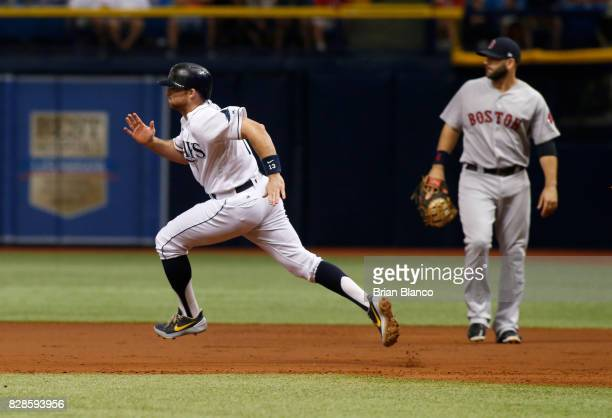 Brad Miller of the Tampa Bay Rays sprints by first baseman Mitch Moreland of the Boston Red Sox after hitting a double during the first inning of a...