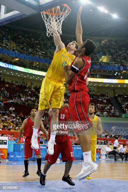 Brad Newley of Australia attempts to dunk as Hamed Ehadadi of Iran blocks during the Men's Preliminary Round Group A basketball game at the Olympic...