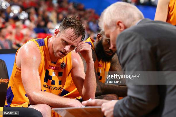 Brad Newley of the Kings looks on as Andrew Gaze addresses the team at a time out late in the fourth quarter during the round 19 NBL match between...