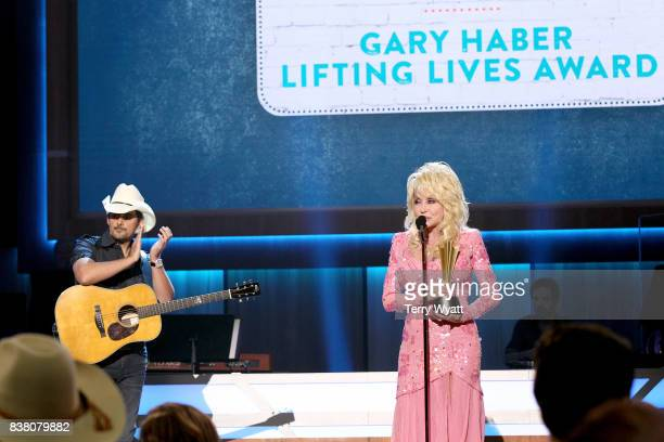Brad Paisley presents Dolly Parton with the Gary Haber Lifting Lives Award onstage during the 11th Annual ACM Honors at the Ryman Auditorium on...