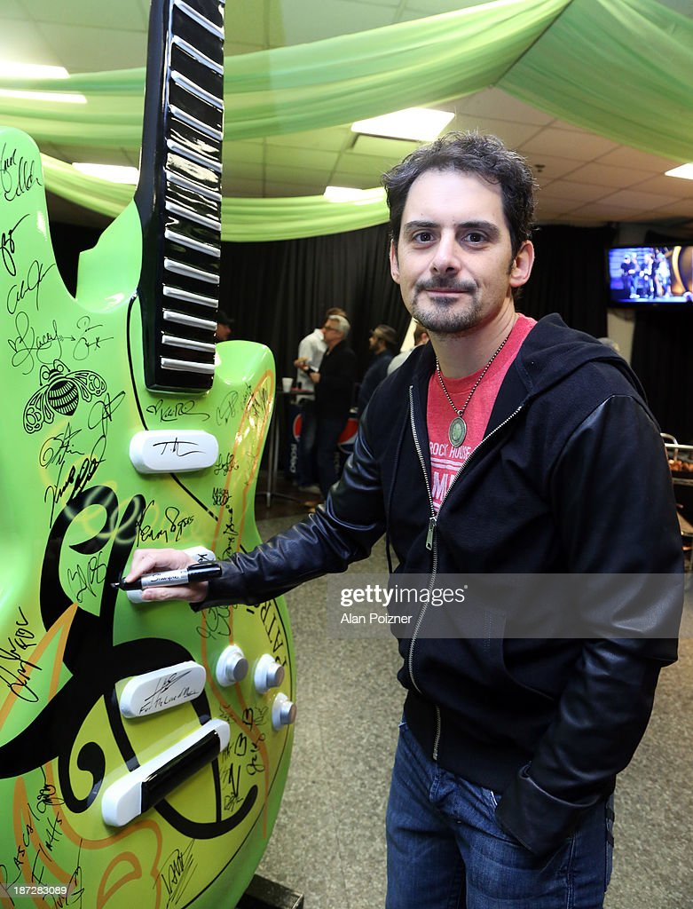 <a gi-track='captionPersonalityLinkClicked' href=/galleries/search?phrase=Brad+Paisley&family=editorial&specificpeople=206616 ng-click='$event.stopPropagation()'>Brad Paisley</a> signs a giant Patron tequila guitar backstage at the CMA Awards to benefit the 'Keep the Music Playing' music education on November 3, 2013 in Nashville, Tennessee.