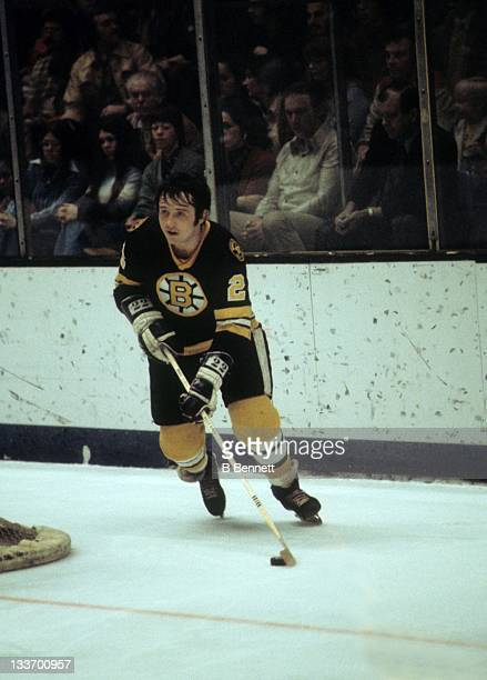 Brad Park of the Boston Bruins skates around the net with the puck during an NHL game circa 1977