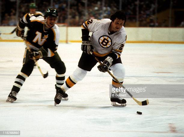 Brad Park of the Boston Bruins skates with the puck as Glen Sharpley of the Minnesota North Stars tracks him down during their game circa 1978 at the...