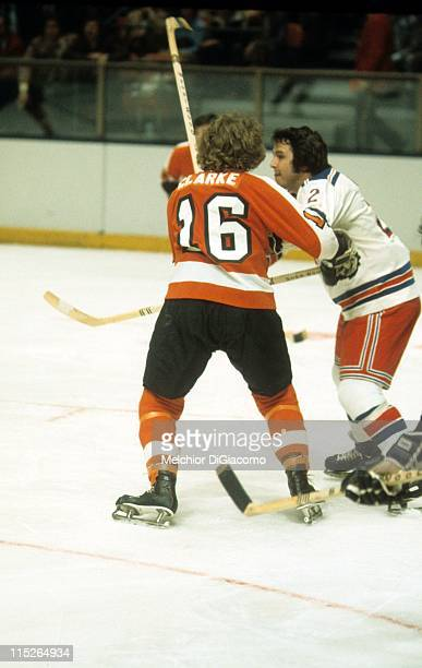 Brad Park of the New York Rangers battles with Bobby Clarke of the Philadelphia Flyers during their game circa 1974 at the Madison Square Garden in...