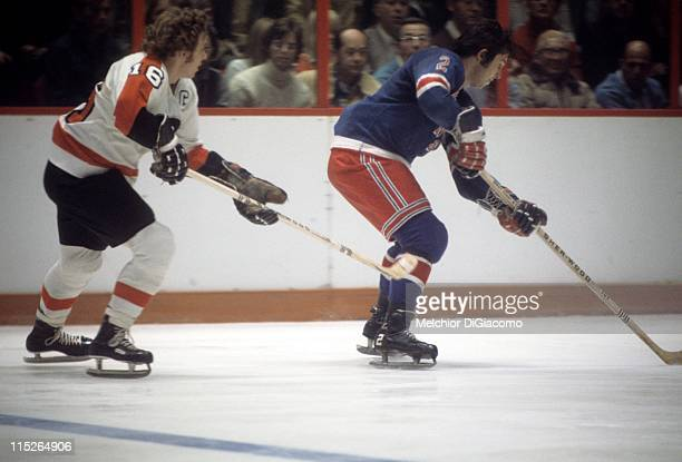 Brad Park of the New York Rangers skates with the puck while being pressured by Bobby Clarke of the Philadelphia Flyers circa 1974 at the Spectrum in...