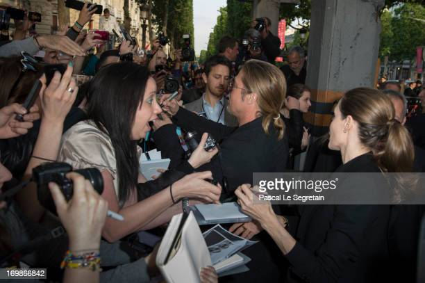 Brad Pitt and Angelina Jolie sign autographs for fans as they arrive for the Paris premiere of 'World War Z' at Cinema UGC Normandie on June 3 2013...