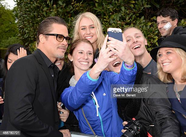 Brad Pitt signs autographs at a private reception as costumes and props from Disney's 'Maleficent' are exhibited in support of Great Ormond Street...