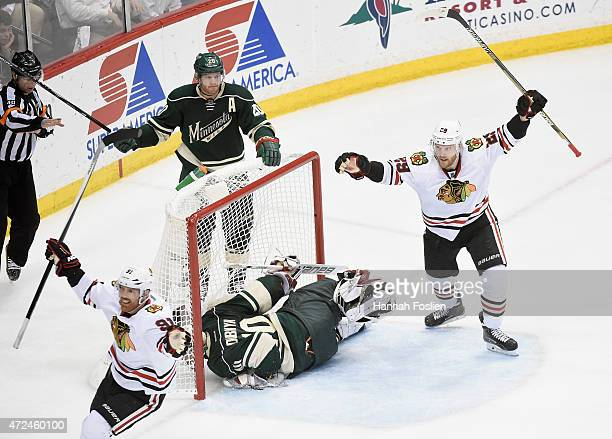 Brad Richards and Bryan Bickell of the Chicago Blackhawks celebrate a goal by teammate Patrick Kane as Ryan Suter and Ryan Suter of the Minnesota...
