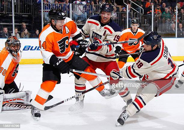 Brad Richards and Marc Staal of the New York Rangers battle for the puck against Kimmo Timonen of the Philadelphia Flyers in the first period at...