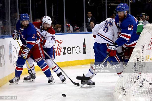 Brad Richards and Martin St Louis of the New York Rangers play the puck against Andrei Markov of the Montreal Canadiens during Game Six of the...