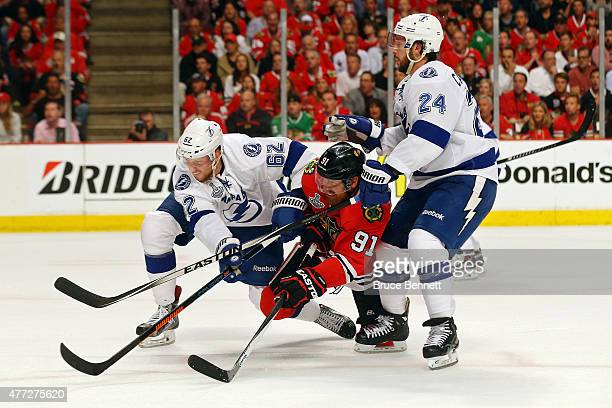Brad Richards of the Chicago Blackhawks fights for the puck against Andrej Sustr and Ryan Callahan of the Tampa Bay Lightning during Game Six of the...