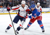 Brad Richards of the New York Rangers and John Erskine of the Washington Capitals battle for the puck in Game Six of the Eastern Conference...